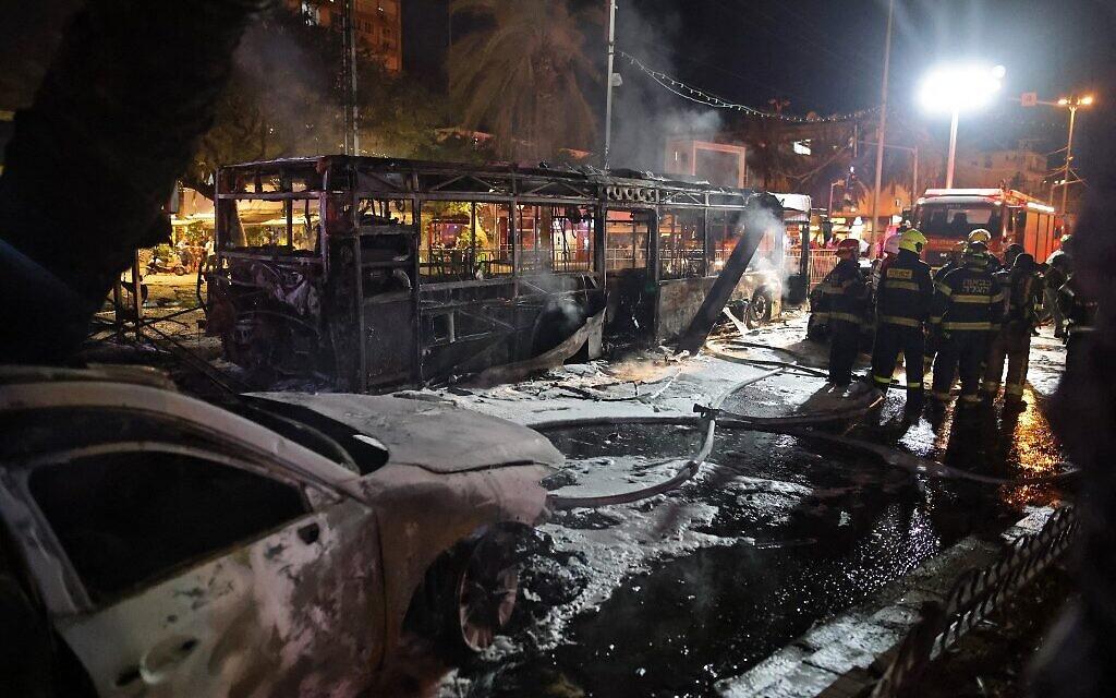 Israeli firefighters near a bus and other vehicles hit in a Gaza rocket strike on Holon near Tel Aviv, on May 11, 2021 (Ahmad Gharabli / AFP)