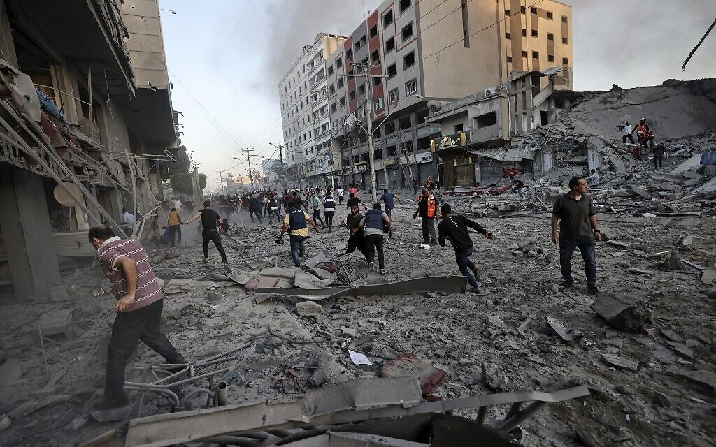 Rescuers and people gather amidst the rubble in front of al-Shourouk tower that collapsed after being hit by an Israeli air strike, in Gaza City, on May 12, 2021 (Mohammed ABED / AFP)