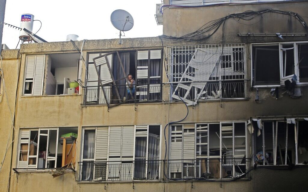 An Israeli man checks the damages in a residential building after a rocket attack from the Hamas-controlled Gaza Strip, in the central Israeli city of Petah Tikva, on May 13, 2021. (GIL COHEN-MAGEN / AFP)