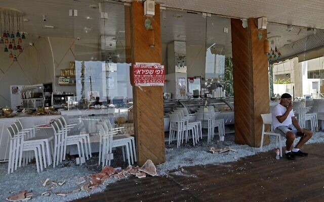 An Israeli man sits at a restaurant that was attacked the previous night in Israel's Mediterranean city of Bat Yam on May 13, 2021 (Gil COHEN-MAGEN / AFP)