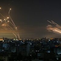 Rockets (R) are seen in the night sky fired towards Israel from Beit Lahia in the northern Gaza Strip on May 14, 2021, while Iron Dome interceptors rise to meet them. (Photo by ANAS BABA / AFP)
