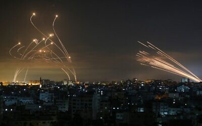 Rockets (l) are seen in the night sky fired towards Israel from Beit Lahia in the northern Gaza Strip on May 14, 2021, while Iron Dome interceptors rise to meet them  (Photo by ANAS BABA / AFP)