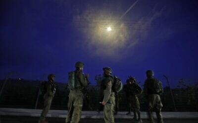 Israeli soldiers stand guard after firing flares above the northern town of Metulla, by the border with Lebanon, following a pro-Palestinian protest across the border in the Lebanese Khiam area, on May 14, 2021 (Jalaa MAREY / AFP)