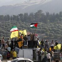 Supporters of Lebanon's Hezbollah lift its flags (C) alongside those of Iran (L) and Palestine, during an anti-Israel protest in the southern Khiam area by the border with Israel, facing the northern Israeli town of Metula, on May 14, 2021. (Photo by Mahmoud ZAYYAT / AFP)