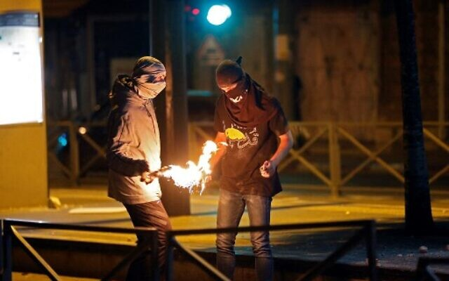 Illustrative: Palestinians light a Molotov cocktail during clashes with Israeli forces in the neighborhood of Shuafat in East Jerusalem, on May 14, 2021. (Ahmad Gharabli/AFP)