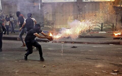 A Palestinian launches flares during clashes with Israeli soldiers in the West Bank city of Hebron on May 14, 2021. (Hazem Bader/AFP)