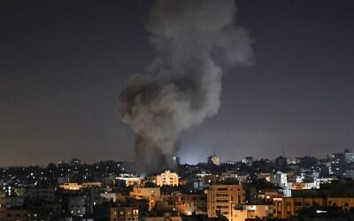 Smoke billows above buildings after an Israeli airstrike on Gaza City in the Gaza Strip early on May 15, 2021. (Photo by MAHMUD HAMS / AFP)