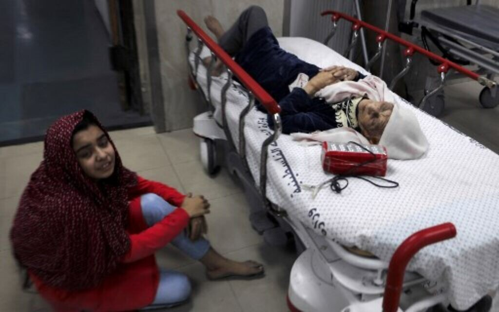 A Palestinian girl sits on the floor next to her wounded grandmother at Al-Shifa Hospital, after an Israeli air strike struck al-Shati Refugee Camp in Gaza City early on May 15, 2021.(Photo by MAHMUD HAMS / AFP)