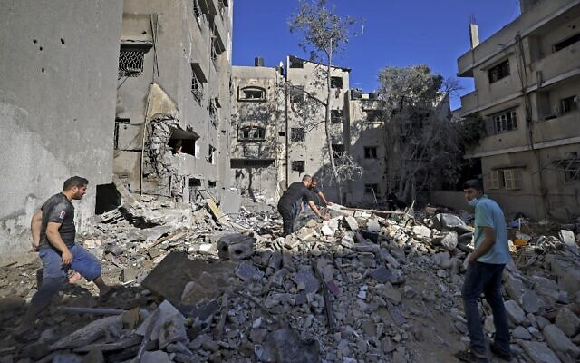 Palestinians look for belongings to salvage among the rubble of a building following Israeli air strikes in Gaza City, on May 15, 2021. (MAHMUD HAMS / AFP)