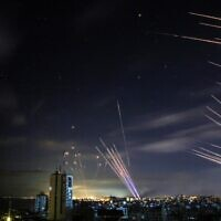 In the background the Israeli Iron Dome missile defense system (L) intercepts rockets (R) fired by the Hamas movement towards southern Israel from Beit Lahia in the northern Gaza Strip, and on foreground tens of other rockets fired by Hamas while the Iron Dome is busy with the first rockets, as seen in the sky above the Gaza Strip overnight on May 16, 2021 (ANAS BABA / AFP)