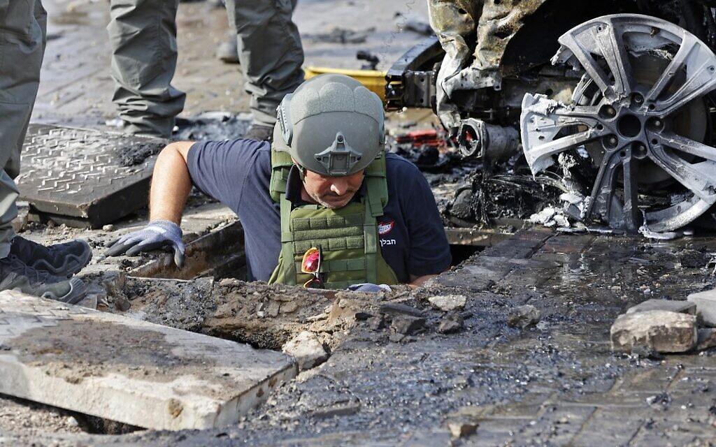 A member of Israeli security forces inspects a crater in the southern Israeli city of Ashkelon following a rocket attack fired from the Gaza Strip, on May 16, 2021. (JACK GUEZ / AFP)