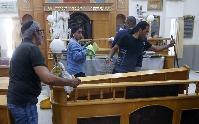 People clean up inside a damaged synagogue in Ashkelon, following a rocket attack from the Gaza Strip, on May 16, 2021. (JACK GUEZ / AFP)