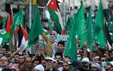 Demonstrators lift flags during a protest to express solidarity with the Palestinian people in the downtown area of the Jordanian capital Amman, on May 16, 2021. (Khalil MAZRAAWI / AFP)