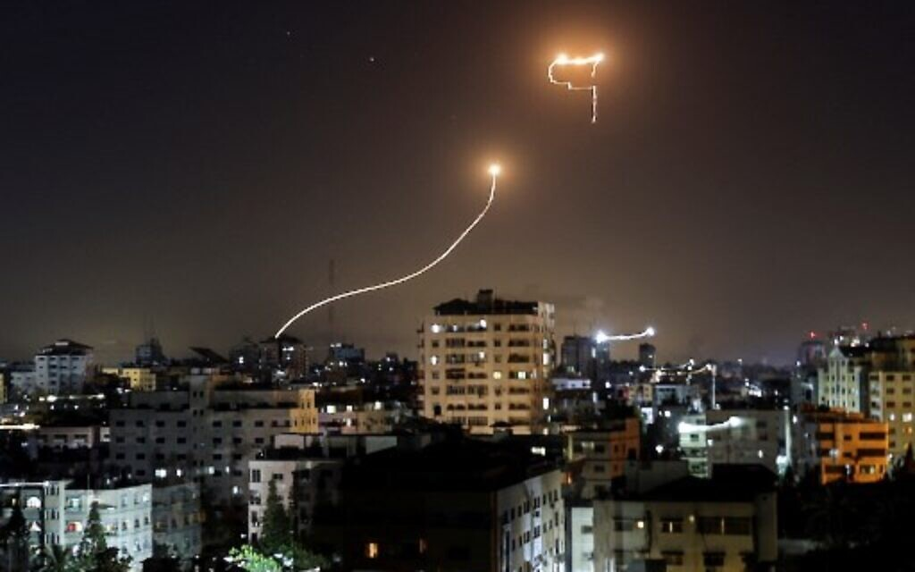 A streak of light appears as Israel's Iron Dome anti-missile system intercepts rockets launched from the Gaza Strip, on May 16, 2021.  (Photo by MAHMUD HAMS / AFP)