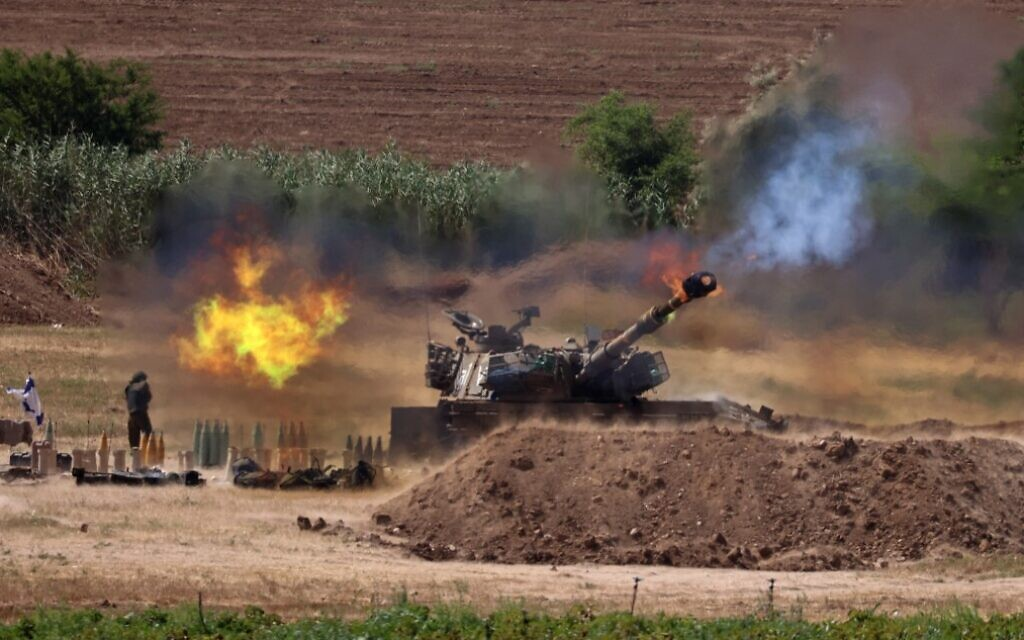 Israeli soldiers fire an artillery piece toward the Gaza Strip from their position along the border with the Hamas-ruled Palestinian enclave, on May 17, 2021. (Emmanuel Dunand/AFP)