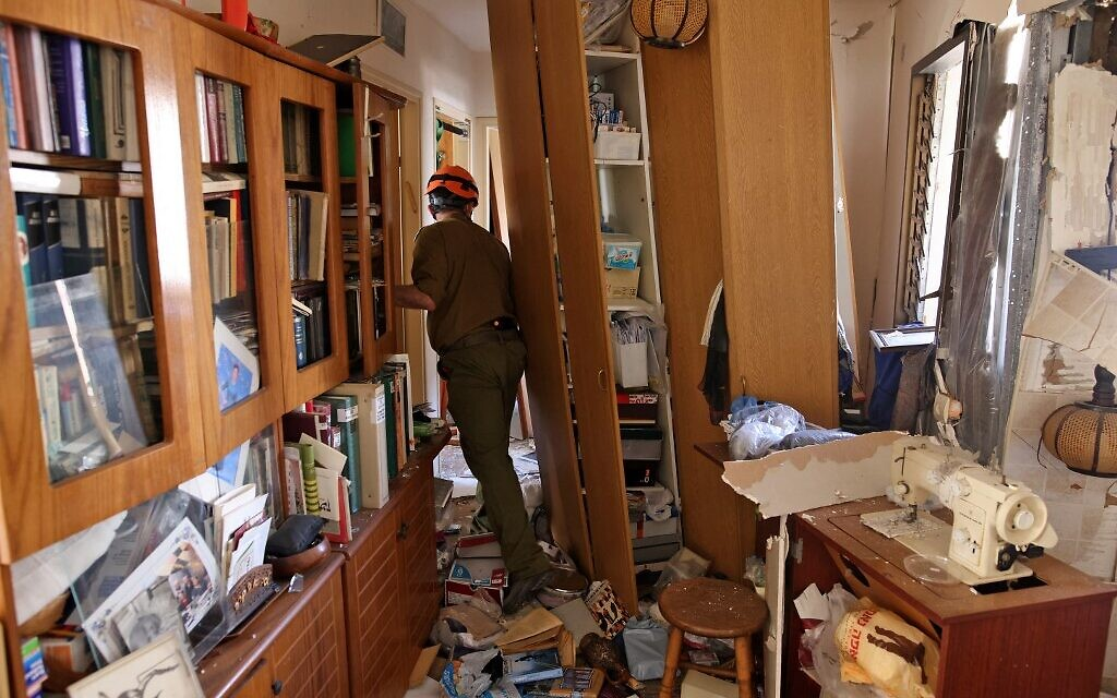 Rescue forces inspect the damage inside an apartment that was hit by a rocket launched from the Gaza Strip on May 17, 2021 in the southern city of Ashdod (Ahmad GHARABLI / AFP)