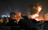 Explosions light-up the night sky above buildings in Gaza City as Israeli forces carry out strikes on the Palestinian enclave, early on May 18, 2021. (Photo by MAHMUD HAMS / AFP)