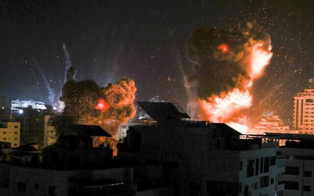 Explosions light-up the night sky above buildings in Gaza City as Israeli forces carry out strikes on the Palestinian enclave, early on May 18, 2021. (MAHMUD HAMS / AFP)