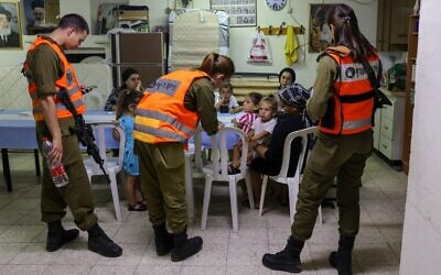 Israeli soldiers from Home Front Command visit families inside a bomb shelter in the southern Israeli city of Ashkelon, on May 18, 2021. (Menahem KAHANA / AFP)