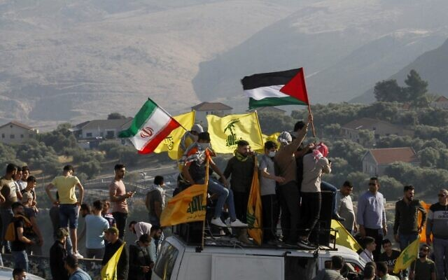 In this file photo taken on May 14, 2021, supporters of Lebanon's Hezbollah lift its flags (C) alongside those of Iran (L) and the Palestinian flag, during an anti-Israel protest in the southern Khiam area by the border with Israel, facing the northern Israeli town of Metula (Mahmoud ZAYYAT / AFP)