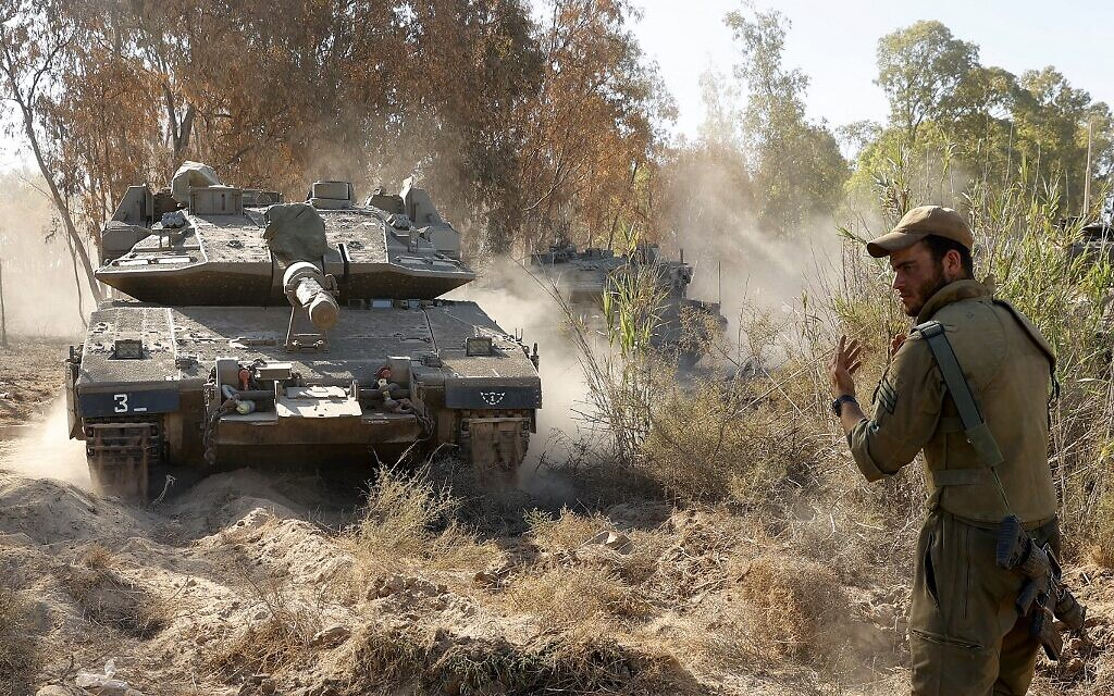 Israeli soldiers direct Merkava tanks to firing positions during shelling towards the Gaza Strip, along the border with the Palestinian enclave on May 19, 2021 (JACK GUEZ / AFP)