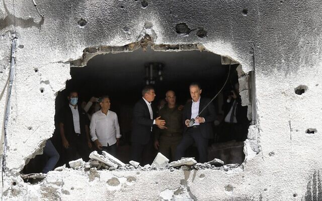 German Foreign Minister Heiko Maas and his Israeli counterpart Gabi Ashkenazi (C) visit a building that was hit by Hamas rocket fire from Gaza, on May 20, 2021, in Petah Tikva. (Gil COHEN-MAGEN / AFP)