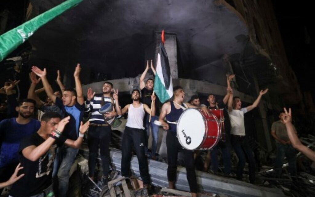 Palestinians celebrate in the streets following a ceasefire between Israel and Hamas, in Gaza City on May 21, 2021.  (Photo by MAHMUD HAMS / AFP)
