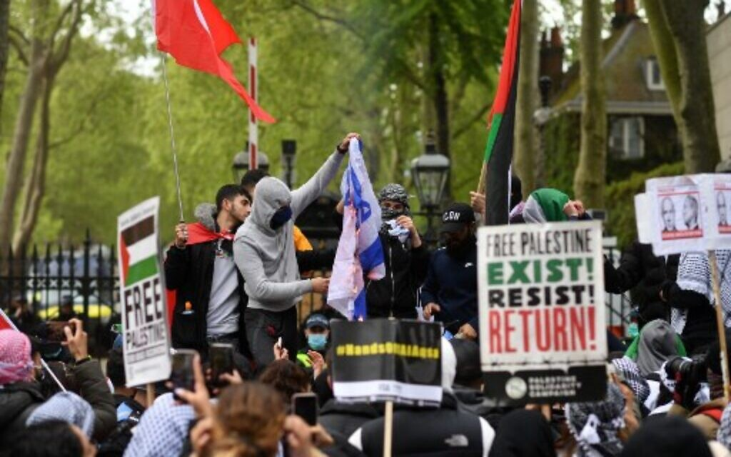 Pro-Palestinian activists and supporters burn an Israeli flag as they demonstrate in support of the Palestinian cause outside the Israeli Embassy in central London on May 22, 2021. (Photo by JUSTIN TALLIS / AFP)