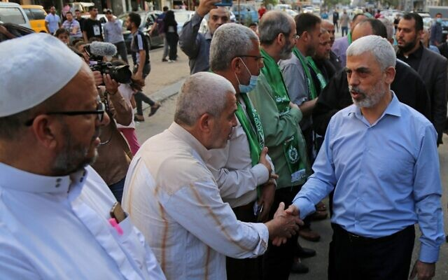 Yahya Sinwar (R), leader of the Palestinian Hamas terror group, is greeted by supporters in Gaza City on May 22, 2021, as he arrives to pay condolences to top Hamas commander Bassem Issa who was killed along others in Israeli airstrikes. (Hatem RAWAGH / AFP)