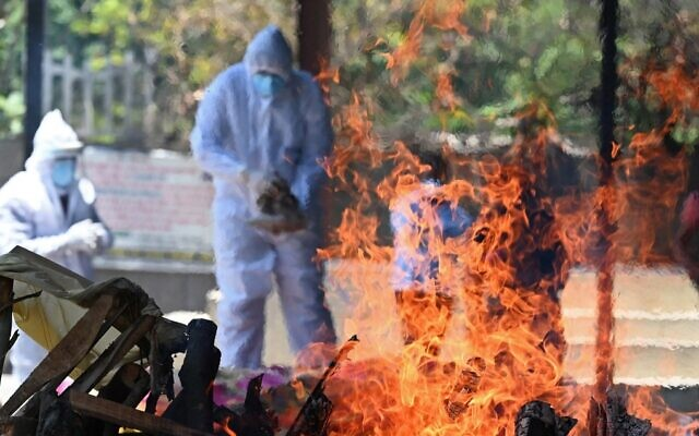 Family members and relatives wearing protective gear stand next to the funeral pyre of a COVID-19 coronavirus victim at a crematorium in New Delhi on May 24, 2021 (Sajjad HUSSAIN / AFP)