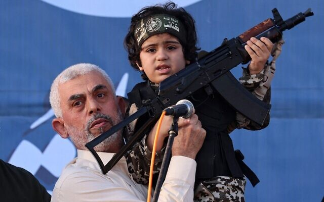 Hamas terror group leader Yahya Sinwar holds the child of an Al-Qassam Brigades member, who was killed in the recent fighting with Israel, during a rally in Gaza City on May 24, 2021. (Emmanuel DUNAND / AFP)