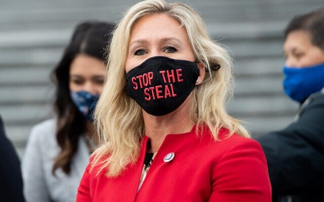 """Republican Rep. Marjorie Taylor Greene of Georgia wears a """"Stop the Steal"""" mask while speaking with fellow first-term Republican members of Congress, on the steps of the US Capitol in Washington, January 4, 2021. (Saul Loeb/AFP)"""