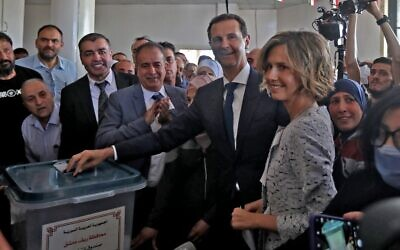 Syrian President Bashar al-Assad and his wife Asma cast their votes at a polling station in Douma, near Damascus on May 26, 2021, as voting began across Syria for an election guaranteed to return Assad for a fourth term in office. (Photo LOUAI BESHARA / AFP)