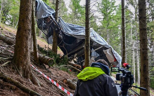 A view shows a journalist working by a cable car's wreckage covered with a tarpaulin on May 26, 2021 on the slopes of the Mottarone peak above Stresa, Piedmont, three days after a crash that killed 14 (MIGUEL MEDINA / AFP)