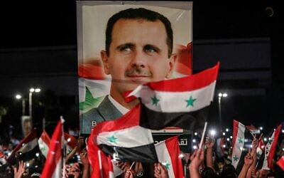 Syrians wave national flags and carry a large portrait of their president as they celebrate in the streets of the capital Damascus, a day after an election set to give the current President Bashar Assad a fourth term, on May 27, 2021 (LOUAI BESHARA / AFP)