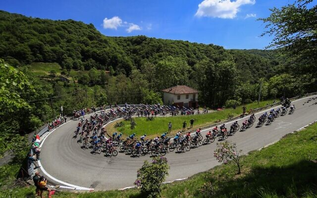 Spectators watch riders of the pack in Sovazza during the 19th stage of the Giro d'Italia 2021 cycling race on May 28, 2021. (Luca Bettini / AFP)