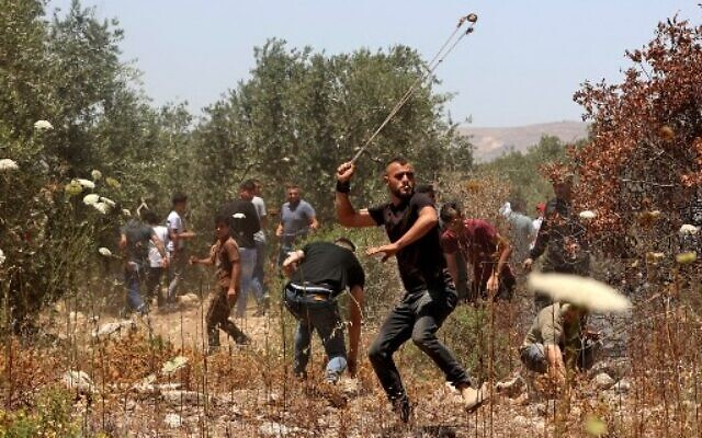 Palestinian protesters use slingshots to hurl stones at Israeli security forces amid clashes in the village of Baita, south of Nablus, in the West Bank on May 28, 2021. (JAAFAR ASHTIYEH / AFP)
