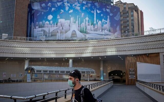 An Iranian walks across a campaign banner hanging on the facade of a building in the capital Tehran on May 28,  2021. - Iran's presidential election campaign officially kicked off, without fanfare and in an atmosphere of indifference as many say the result is a foregone conclusion. ( AFP)