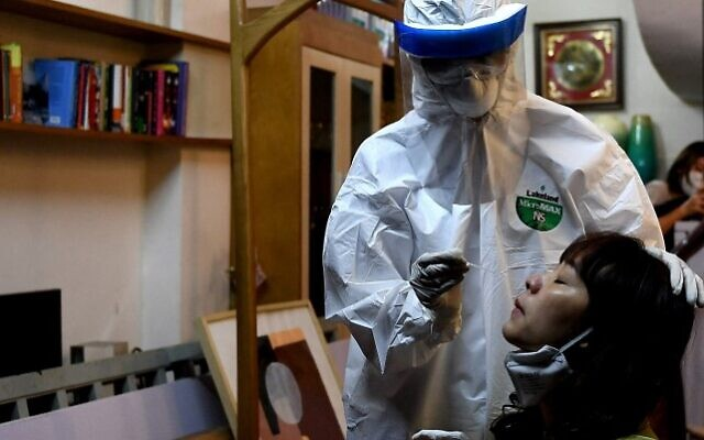 In this file photo taken on March 30, 2020, a health worker, wearing protective clothing amid concerns of the spread of the COVID-19 coronavirus, conducts a swab test on a woman in her house in Hanoi, Vietnam. (Nhac NGUYEN / AFP)