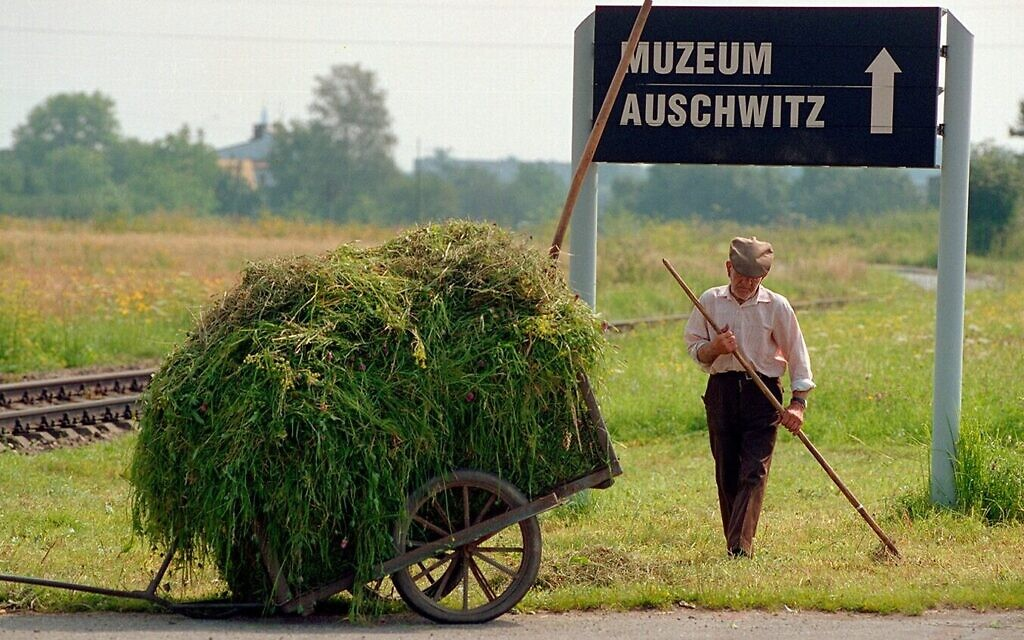 A groundskeeper working beside the train tracks that lead to Auschwitz in this still from the 1998 documentary 'The Last Day.' (Courtesy)