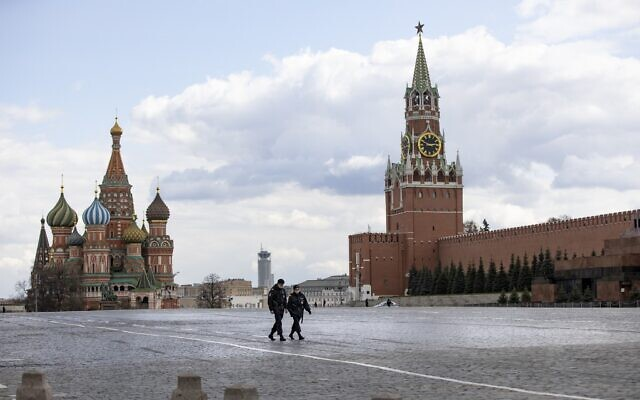 Two police officers patrol an almost empty Red Square, with St. Basil's Cathedral, center, and Spasskaya Tower in Moscow, Russia, April 20, 2020 (AP Photo/Alexander Zemlianichenko)