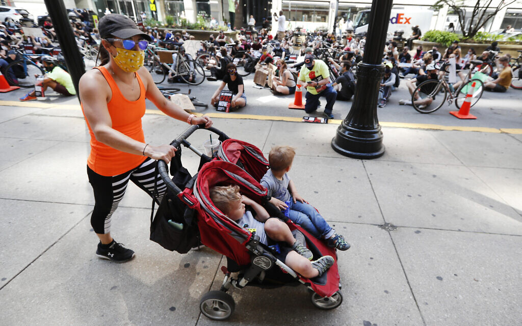 Illustrative: A woman and two children pass protesters sitting on La Salle Street in front of Chicago's City Hall, Wednesday, June 17, 2020 (AP Photo/Charles Rex Arbogast)