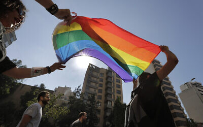 Activists from the Lesbian, Gay, Bisexual, and Transgender  (LGBT) community in Lebanon shout slogans and hold up a rainbow flags as they march in which they are calling on the government for more rights in the country gripped by economic and financial crisis during ongoing protests in Beirut, Lebanon,  June 27, 2020. (AP Photo/Hassan Ammar)