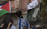 A man holding the Israeli flag shouts at protesters waving the Palestinian flag during a demonstration against the expulsion of Palestinian families from their homes in the East Jerusalem neighborhood Sheikh Jarrah, April 16, 2021. (AP Photo/Maya Alleruzzo)