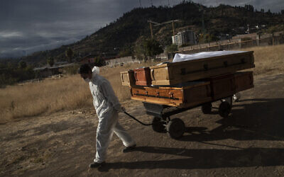 A funeral worker removes empty coffins that held remains that were later cremated amid the coronavirus pandemic, at La Recoleta cemetery in Santiago, Chile, April 21, 2021. (Esteban Felix/AP)