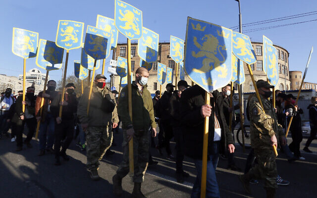 Marchers hold up the symbol of the 14th Waffen Grenadier Division of the SS in Kyiv, Ukraine on April 28, 2021. (AP Photo/Efrem Lukatsky)