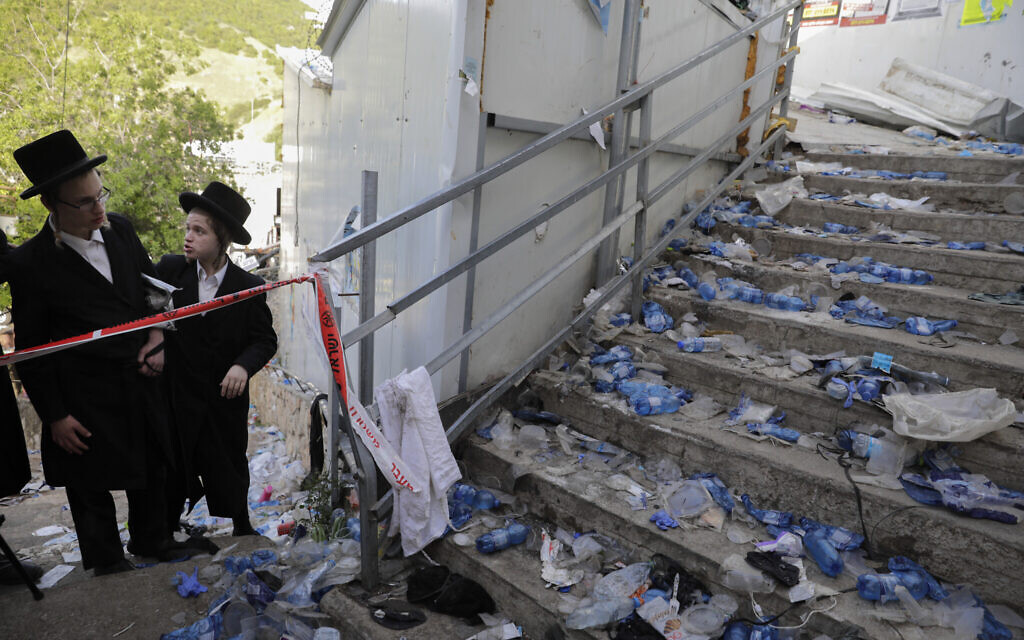 Ultra-Orthodox Jews stand at the bottom of a staircase, leading from a narrow walkway where a crush led to mass fatalities at Lag B'Omer celebrations at Mt. Meron in northern Israel, Friday, April 30, 2021. (AP Photo/Sebastian Scheiner)