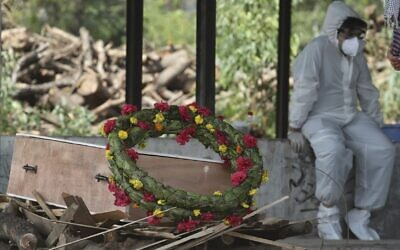 A wreath lies on the coffin of a COVID-19 victim before his cremation in Jammu, India, Friday, April 30, 2021 (AP Photo/Channi Anand)
