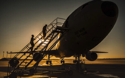 Two KC-10 Extender crew chiefs board the aircraft at Al-Dhafra Air Base, United Arab Emirates, January 5, 2021. (US Air Force/Staff Sgt. Trevor T. McBride, via AP)