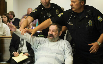 Frazier Glenn Miller Jr., convicted of capital murder, attempted murder and other charges, gestures as Johnson County deputies remove him from the courtroom during the sentencing phase of his trial at the Johnson County District Court in Olathe, Kan. November 10, 2015. (Joe Ledford/The Kansas City Star via AP, Pool, File)